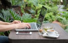 Frau mit Laptop und Smartphone im Grünen