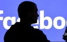Mann steht vor Facebook-Logo