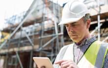 Bauarbeiter mit mobilem Gerät in der Hand